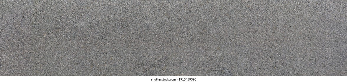 Background and texture of the road surface is made of asphalt and small stones.