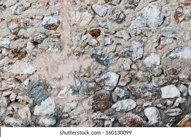 Background texture of a rock wall with rough uncut stones and pebbles of all shapes and sizes arranged randomly