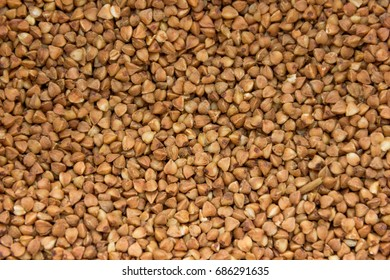 Background, texture, the rump. Buckwheat grains. Roasted buckwheat. Useful properties of buckwheat. Garnish. Ingredient, product, cook. Brown. crop, organic farming. Dietary product. Close up.