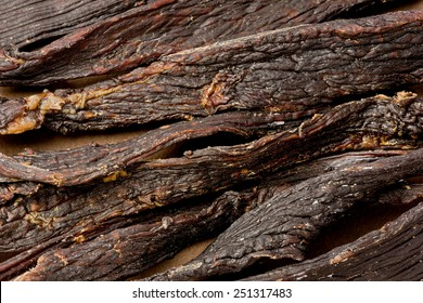Background texture of several pieces of black pepper beef jerky.