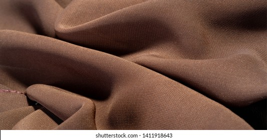 Background texture of silk fabric. This is a natural brown scarf, this beautiful nylon satin made of artificial silk with a clear hand and a wonderful sheen is perfect for your projects.