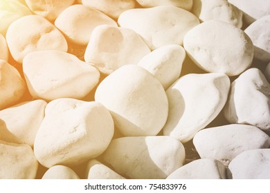 Background texture of smooth white stones or rocks used in landscaping and construction for decoration in a close up full frame view with the sun glow in the top left corner