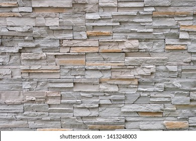 Background texture, Stone cladding wall made of stacked stripes rocks. The colors are from white gray and brown.