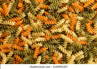Background texture of tricolor fusilli pasta for traditional Italian and Mediterranean cuisine in a close up full frame view