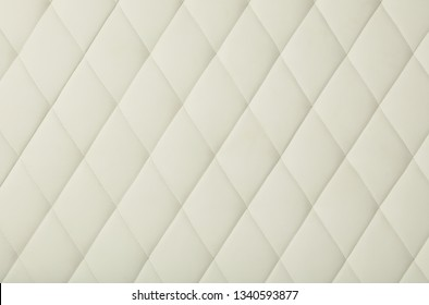 Background texture of white leather soft tufted furniture or wall panel upholstery with deep diamond pattern, close up