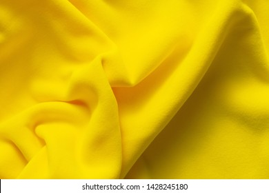 Background texture of yellow fleece, soft napped insulating fabric made of polyester, wavy pattern, top view