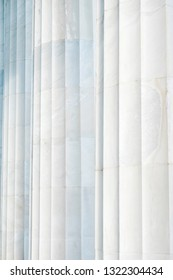 A background that shows the subtle coloring and the fluting on three white marble columns at the Lincoln Memorial in Washington DC.
