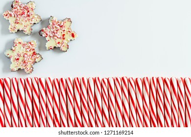 Background of three chocolate peppermint bark snowflakes with row of red and white striped peppermint candies and copy space