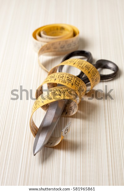 background with tools for sewing: scissors and tape measure