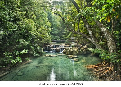 Background of tropical jungle. Erawan waterfall is located at not deep forest of Thailand. Environment of the jungle has leafy, clear water and a lot of fish.it call tropical rainforest in kanchanabur