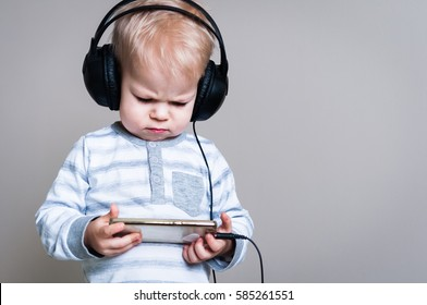 Background with two years old displeased boy listens to music in headphones, holding in hands the smartphone.