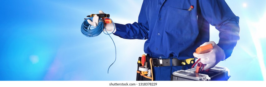 Background with uniformed electrician with tools and electrical equipment and blue background. Front view.