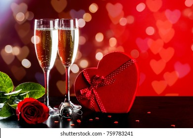 Background of Valentines day celebration with champagne, rose, heart shaped present and red candies.