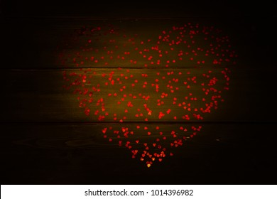 Background for Valentine's Day. Heart of red cofetti on wooden boards.