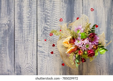Background Valentine's Day or wedding. Basket bouquet of roses and chrysanthemums on a vintage wooden background. Flat lay. Top view with copy space.