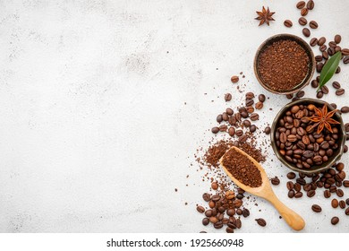 Background of various coffee , dark roasted coffee beans , ground and capsules with scoops setup on white concrete background with copy space.