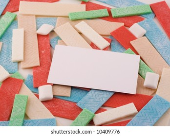 A background of various sticks and pieces of gum support a blank white business card.