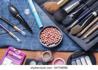 background various women's beauty accessories lie on denim