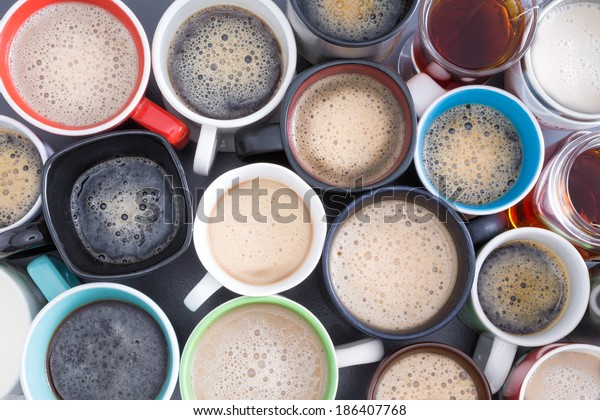 Background with a view from above of closely packed assorted mugs full of fresh hot coffee covered in froth