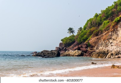 Background with a view of the beautiful beach with a rocky and a palm tree in Vasco da Gama. Goa, India