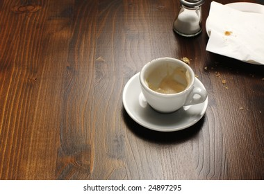 A background with a view of an empty coffee cup on a wooden table.