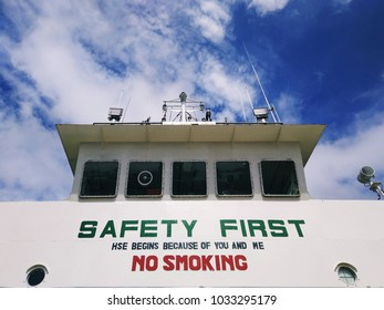 """Background view of a safety slogan """"Safety First, HSE begins because of you and me and No Smoking"""" on board a marine vessel."""