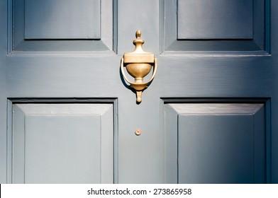 Background of vintage blue painted door and knocker vignette look