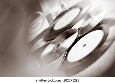 Background with Vinyl record discs ans CD. Focus on foreground. Black and white image with view through CD hole
