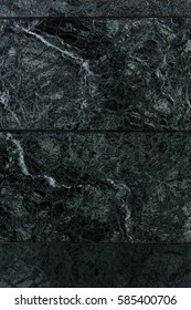 Background wall of flat of polished natural marble. Unusual texture, beautiful deep stains of different layers on background of black marble slabs. Background luxury and wealth of interior decoration