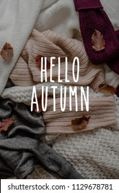 Background with warm sweaters and the inscription HELLO AUTUMN. Pile of knitted clothes with autumn leaves, warm background, knitwear, Autumn concept.