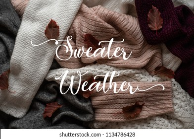 Background with warm sweaters and the inscription SWEATER WEATHER. Pile of knitted clothes with autumn leaves, warm background, knitwear, Autumn concept.