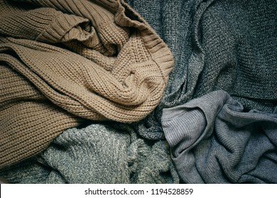 Background with warm sweaters and the inscription SWEATER WEATHER. Pile of knitted clothes , warm background, knitwear, Autumn concept. Top view