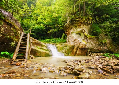 Background with waterfall in mountains with forest.