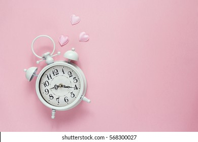 Background with white alarm clock and hearts on pink. Place for text. Top view. Time for love and greetings.