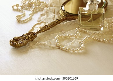 Background of white delicate lace fabric, perfume, hand mirror and white flowers