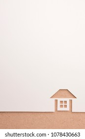 background of white paper cutout in complete house shape in brown color ground, for home and insurance conceptual.