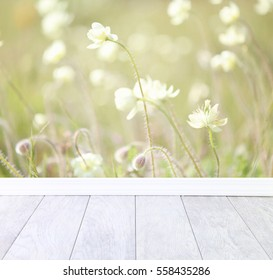 A background of wildflowers and a ceramic wood floor in the foreground.  A photographers backdrop.