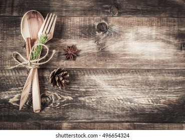Background wooden cutlery and fir-cone on a wooden background