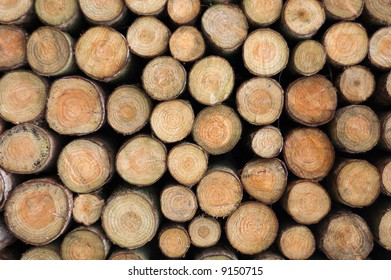 Background of wooden logs piled up into a stack