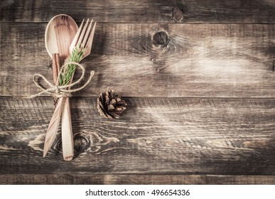 Background wooden spoon and fork, fir-cone on a wooden background