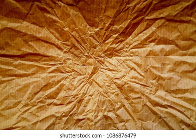 A background of wrinkled brown wrapping paper with creases radiating from the center. Processed with saturated colors and contrast for effect