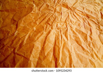 A background of wrinkled brown wrapping paper. Photographed with side light and processed with saturated colors and contrast for effect