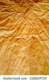 A background of wrinkled brown wrapping or parcel paper. Photographed with side lighting and processed with saturated colors for effect