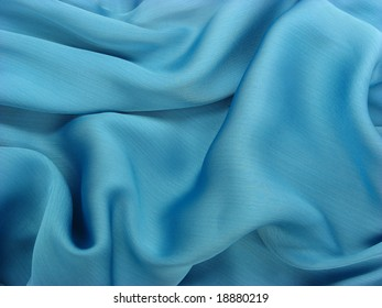 Background of wrinkled shiny blue fabric