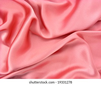 Background of wrinkled shiny pink fabric close up details