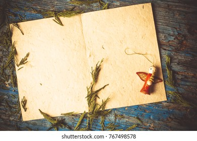 Background for write Christmas greeting or put photo rustic style. Blank paper parchment and vintage Christmas ornaments on rustic wooden table.