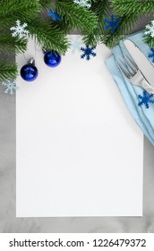 Background for writing the Christmas Menu. Winter Table Setting. Christmas tree, cutlery and blank paper. Top View, Copy Space.