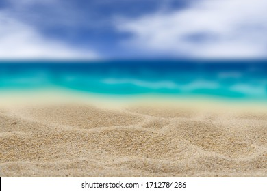 Background. Yellow sand on a blurred turquoise sea background. Cloudy sky Free space for any material.