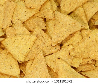 background of yellow tortilla chips made with corn vegetables oils and salt