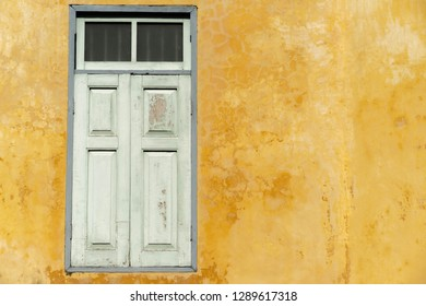Backgrounds Old wooden windows on the yellow wall